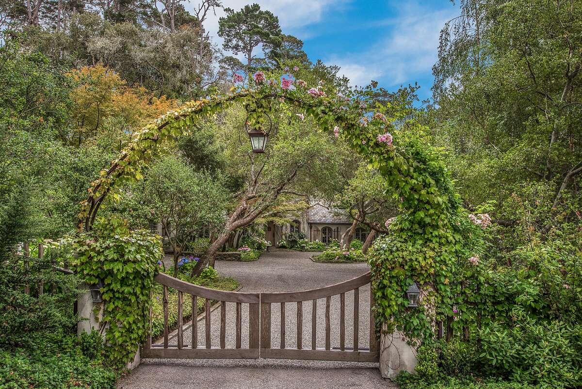 A rose covered wrought-iron arched entry gate built by John Hudson of Point Lobos Forge waits before the home.�