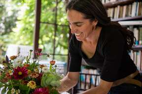 Joanna Letz arranges floral table centerpieces she made for her sister�s wedding, on Saturday, June 9, 2018.