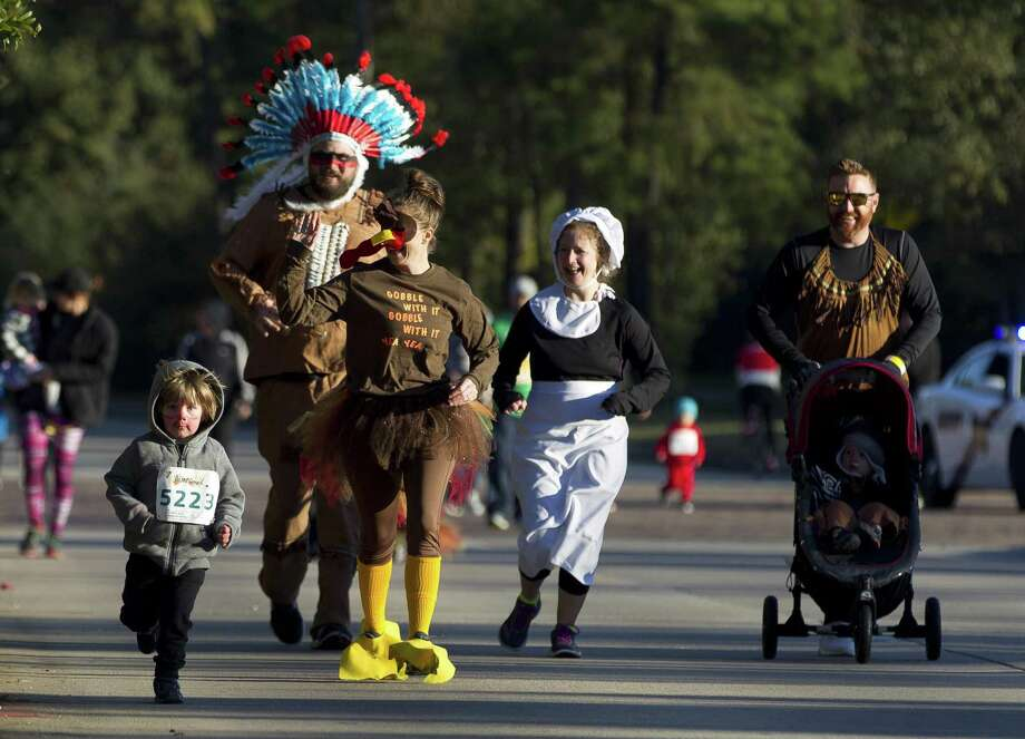 Denise Smith, second from left, Ricky Henry, Sarah Klepper and Zach Klepper wear festive outfits as they take part in the annual YMCA Run Thru the Woods on Thanksgiving, Thursday, Nov. 23, 2017, in The Woodlands. Registration is now open for this year's race which is scheduled for Thursday, Nov. 22. Photo: Jason Fochtman, Staff Photographer / Houston Chronicle / © 2017 Houston Chronicle