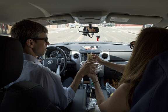 Amy O'Rourke, right, hands a burrito to her husband, Beto O'Rourke, as they drive roughly 70 miles to the third campaign stop of the day Tuesday, July 31, 2018, in Lubbock, Texas. The O'Rourkes later headed to Muleshoe after the town hall at the Cactus Theater.