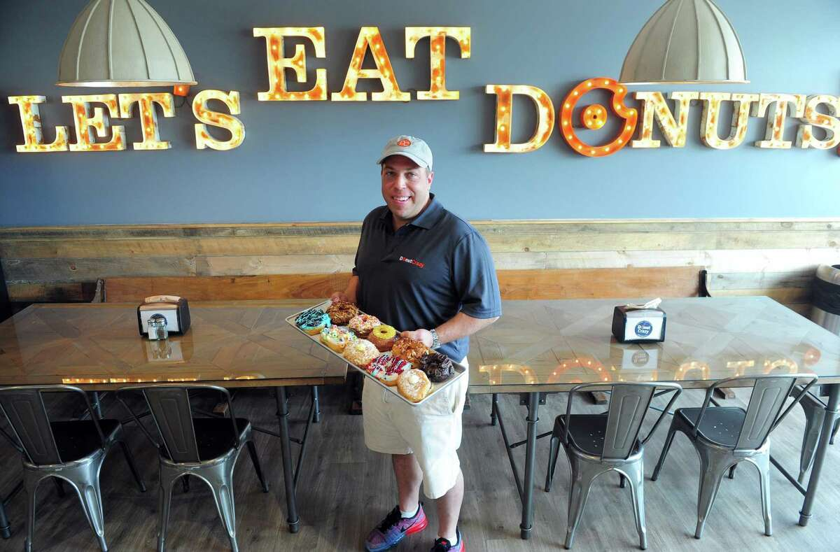 Owner Jason Wojnarowski holds a sampling of fresh-made doughnuts at Donut Crazy, a new shop on River Road in Shelton, Conn., across from Sports Center of Connecticut.