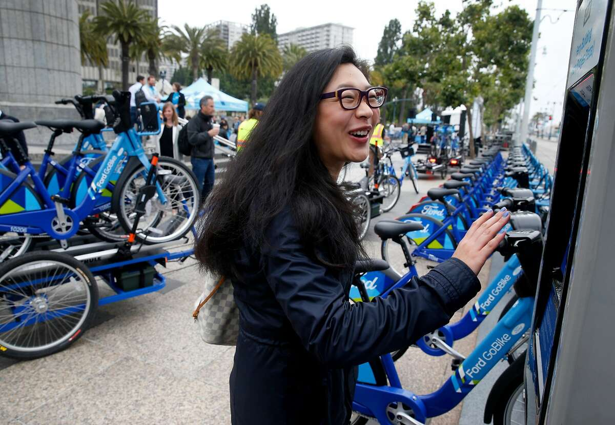 Shirley Qian operates the control panel of a Ford GoBike docking station in front of the Ferry Building in San Francisco, Calif. on Wednesday, June 28, 2017. Qian, an East Bay resident, thinks it's a great idea to have bicycles readily available close to public transit connections. The Bay Area-wide bike sharing service, which plans a fleet of 3,500 bicycles by Labor Day and as many as 7,000 by the end of 2018, went into service today.