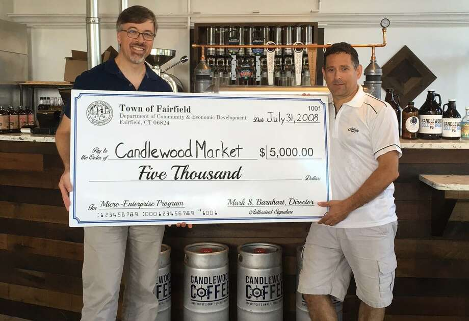 Community and Economic Development Mark Barnhart, left, and Candlewood Market owner Tony Inzero show off a big check that represents a microgrant the business received from the town. Photo: Contributed / Contributed Photo / Fairfield Citizen