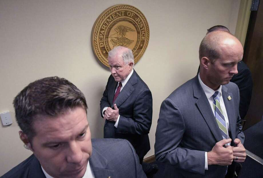 Attorney General Jeff Sessions walks past law enforcement officials as he arrives to deliver remarks on efforts to combat violent crime in America during an appearance at the United States Attorney's Office for the Middle District of Georgia on Thursday August 9, 2018, in Macon, Ga. (AP Photo/John Amis) Photo: John Amis, FRE / Associated Press / FR69715 AP