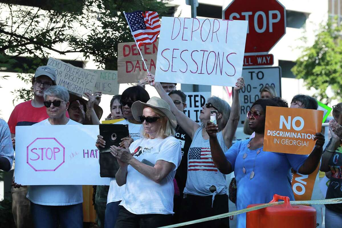 Several dozen protesters gather across the street from the U.S. Attorney's Office for the Middle District of Georgia during a visit by Attorney General Jeff Sessions on Thursday, Aug. 9, 2018, in Macon, Ga. (Curtis Compton/Atlanta Journal-Constitution/TNS)