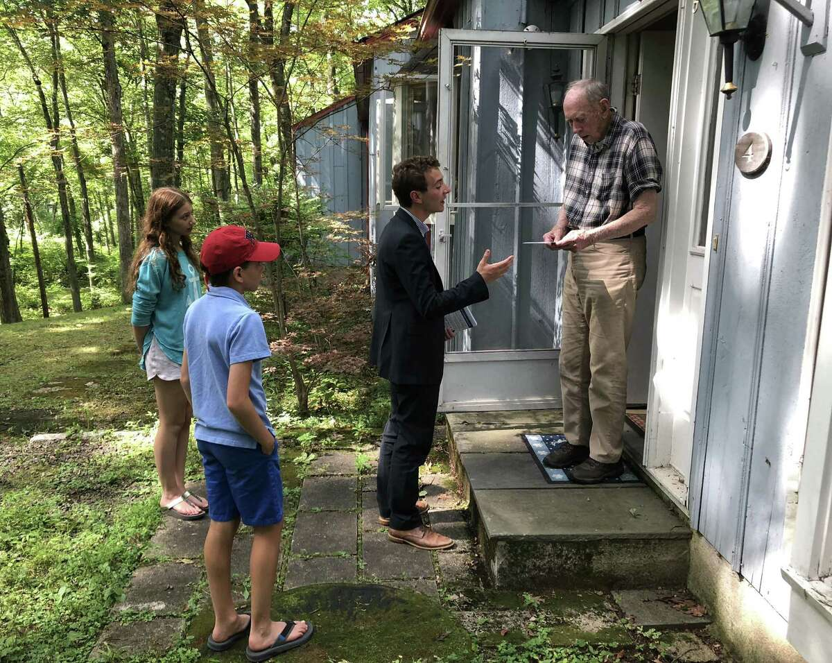 Will Haskell, the Democratic candidate for the 26th state senate district, knocks on doors in Westport on July 31 with campaign volunteers and New Canaan residents Leila and Cyrus Pearson.