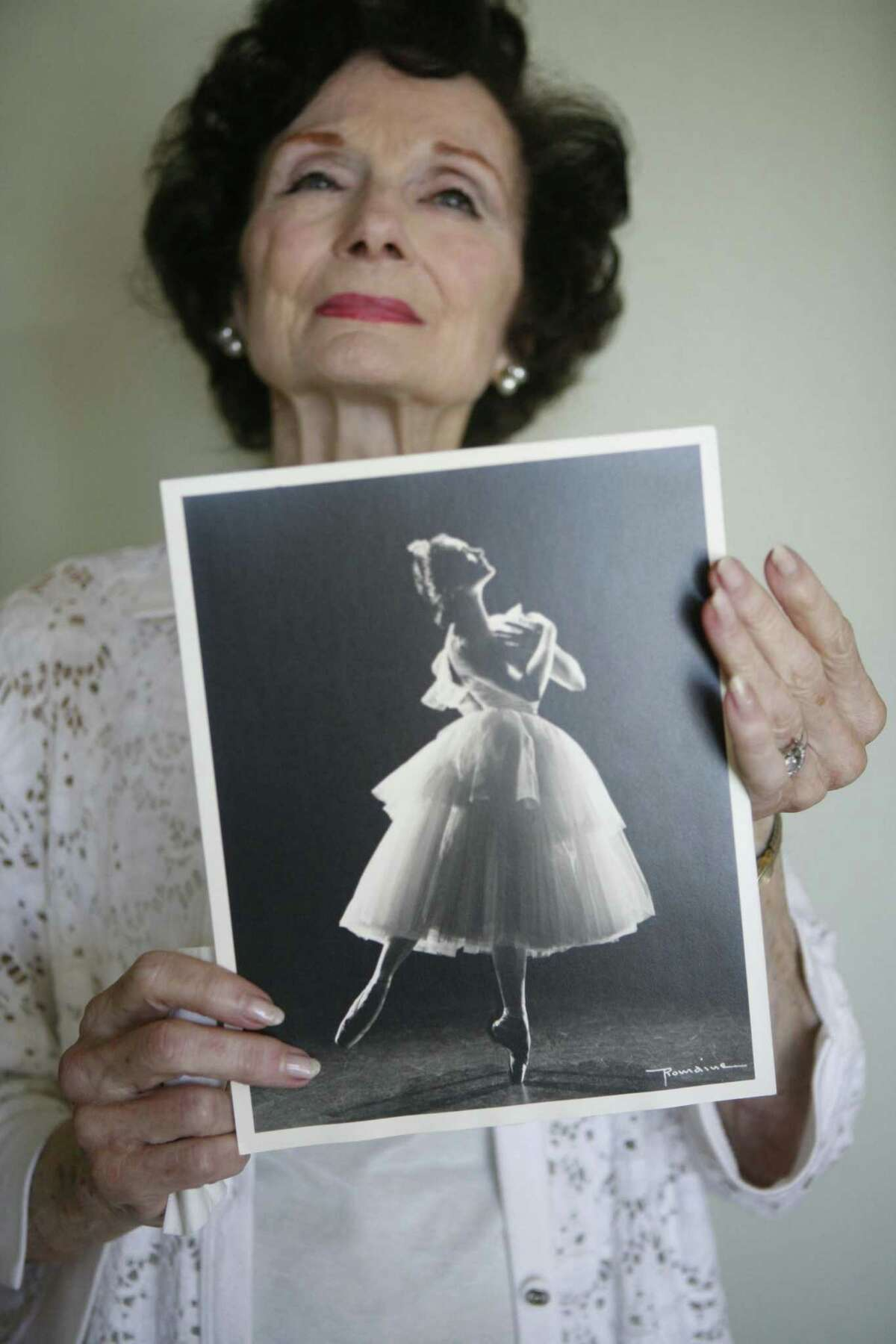 Jocelyn Vollmar, at 82, holding a photo taken of herself in the 1950s.