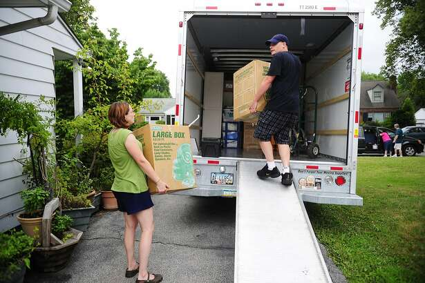 FILE- In this July 13, 2012, file photo, people load a U-Haul truck with boxes while they prepare to move in York, Pa. Moving to a new place can be taxing, emotionally and financially. Preparing a budget can help. (Chris Dunn/York Daily Record via AP)