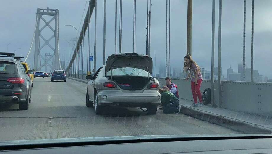 A family attempts to change a flat tire on the Bay Bridge late last month. (Photo courtesy of Everett Chan.) Photo: Everett Chan