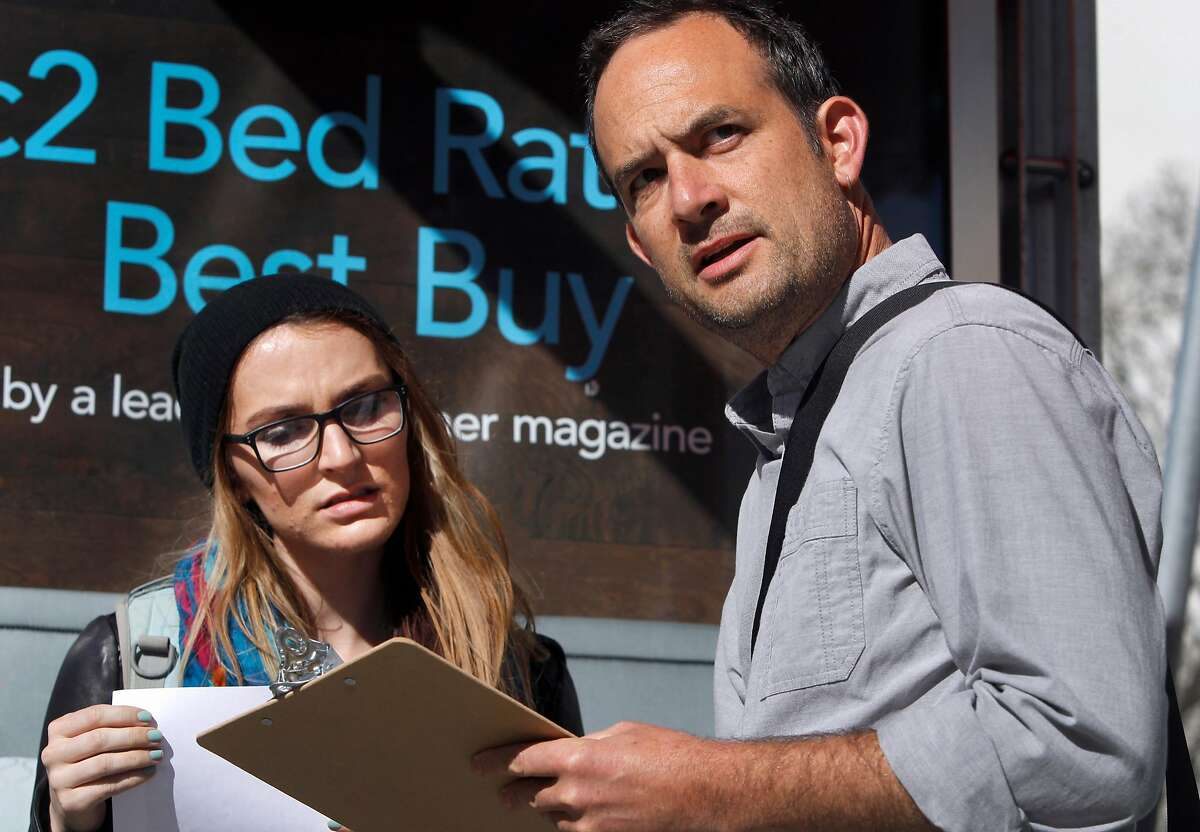 Artist Scott Oliver (right) interviews commuter Tirzah Duren while she waits at a bus stop on Geary Boulevard and Masonic Avenue in San Francisco, Calif. on Thursday, March 12, 2015.