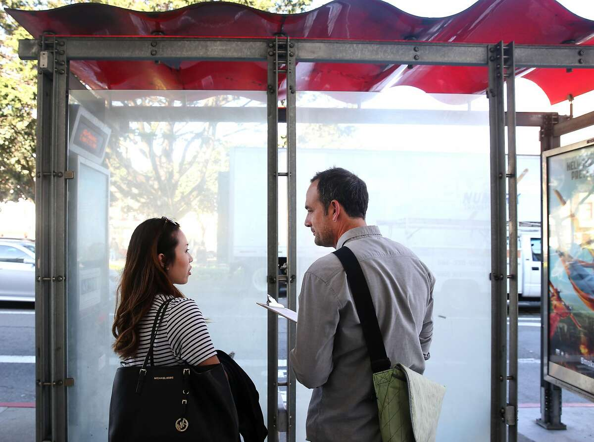 Artist Scott Oliver (right) interviews a commuter, who said her name is Emily, while she waits at a bus stop on Masonic Avenue and Geary Boulevard in San Francisco, Calif. on Thursday, March 12, 2015.