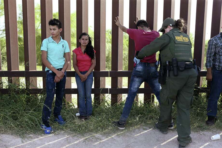Santos Abel Madrigez, 34, center left and her son, Nelson Ortez, 17, wait as U.S Border Patrol Agent Amber Peterson pats-down another immigrant by the border wall in Hidalgo County, Texas, Thursday, July 19, 2018. They were with a group of seven immigrants from Central America, turned themselves into authorities after illegally crossing the Rio Grande into the U.S. The group included family units. Photo: JERRY LARA / San Antonio Express-News / San Antonio Express-News