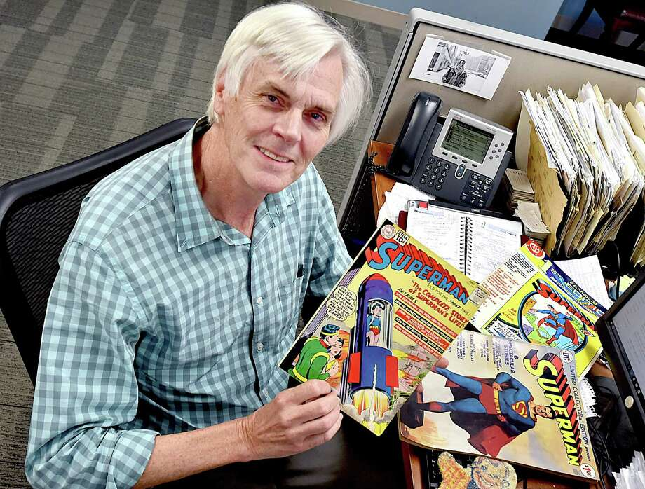 Randall Beach at his desk at the New Haven Register with some of the comic books and Howdy Doody towels he did not sell. Photo: Catherine Avalone / Hearst Connecticut Media / New Haven Register