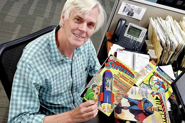 Randall Beach at his desk at the New Haven Register with some of the comic books and Howdy Doody towels he did not sell.