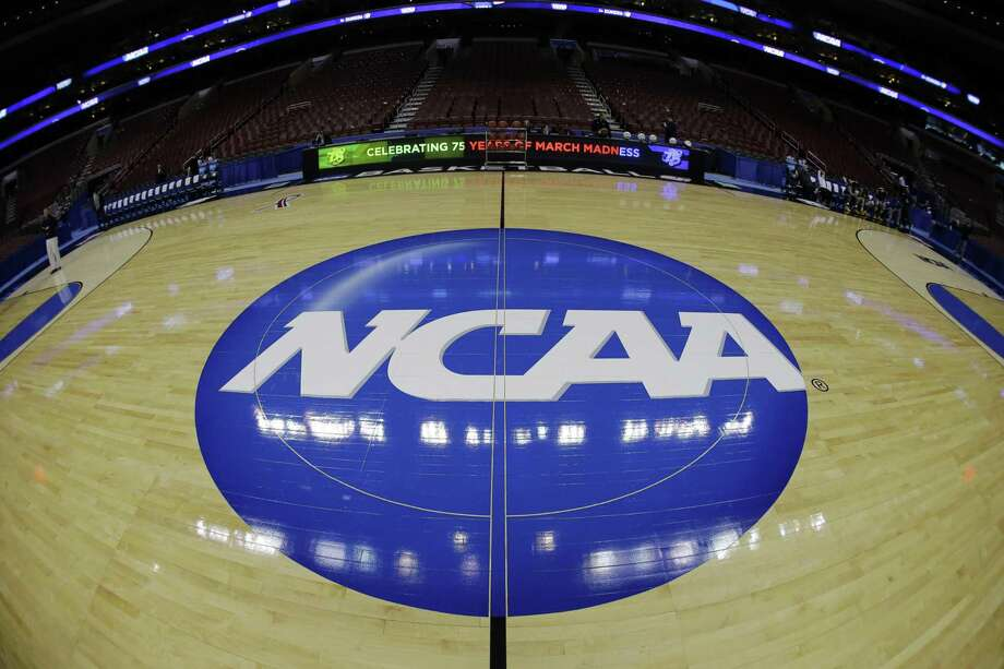 FILE - In this March 21, 2013, file photo, taken with a fisheye lens, the NCAA logo is displayed on the court during the NCAA college basketball tournament in Philadelphia. College basketball players who go undrafted by the NBA will be allowed to return to school and play as part of sweeping NCAA reforms in the wake of a corruption scandal, the NCAA announced Wednesday, Aug. 8, 2018. (AP Photo/Matt Slocum, File) Photo: Matt Slocum / Associated Press / Copyright 2018 The Associated Press. All rights reserved.