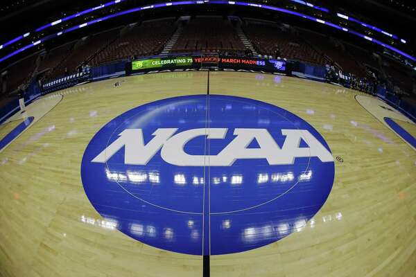 FILE - In this March 21, 2013, file photo, taken with a fisheye lens, the NCAA logo is displayed on the court during the NCAA college basketball tournament in Philadelphia. College basketball players who go undrafted by the NBA will be allowed to return to school and play as part of sweeping NCAA reforms in the wake of a corruption scandal, the NCAA announced Wednesday, Aug. 8, 2018. (AP Photo/Matt Slocum, File)