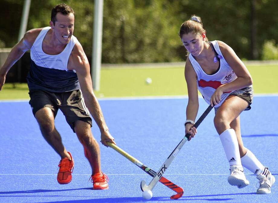 "Vivi Caruso of Greenwich uses her ball skills to defend against Mike Barminski, a member of the USA National Mens Field Hockey Team during a scrimmage following a ""Learn to Play Field Hockey"" Thursday in Greenwich. Photo: Matthew Brown / Hearst Connecticut Media / Stamford Advocate"