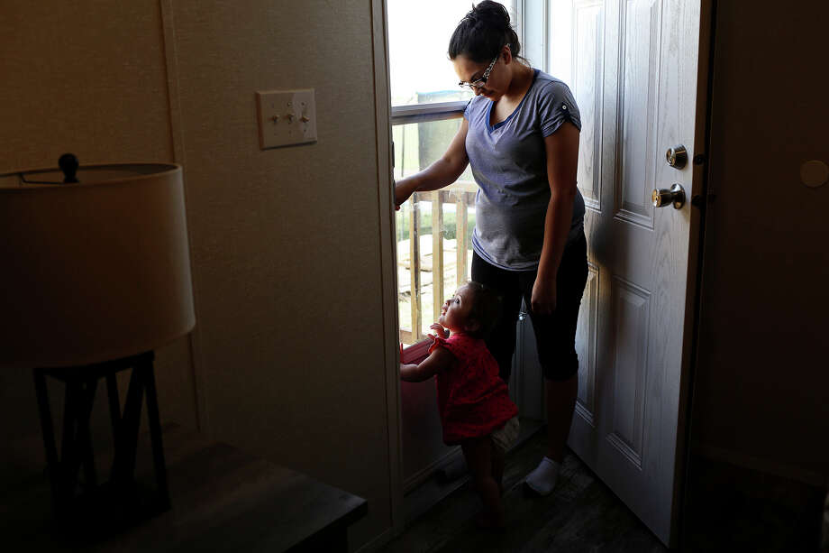 Danielle Kelley waits to let her dog, Cha be-be, back in with her daughter, Raeleigh, 1, at her home in Cibolo on July 10, 2018. (Lisa Krantz | San Antonio Express-News) / San Antonio Express-News