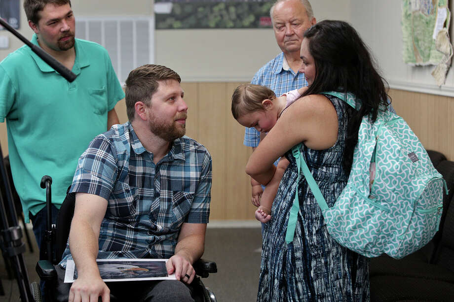 Danielle Kelley holds her daughter, Raeleigh, as she talks with Kris Workman, who was paralyzed by a shot fired by Kelley, after the first service Kelley attended at First Baptist Church of Sutherland Springs, since the Nov. 5 shooting, on June 17, 2018. (Lisa Krantz | San Antonio Express-News) / San Antonio Express-News