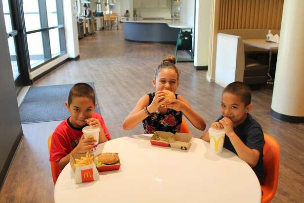 Andrew and AJ, both 7, and Briella, 8, eat their meals at the Palo Alto Ronald McDonald House.