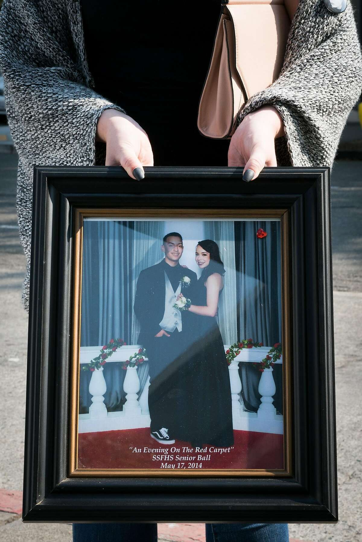 Whitney Welch holds a photo of 20-year-old Ghost Ship fire victim, Michela Gregory, outside of the sentencing hearing of defendants, Derick Almena and Max Harris at the Rene C. Davidson Courthouse in Oakland, Calif. on Thursday, August 9, 2018.
