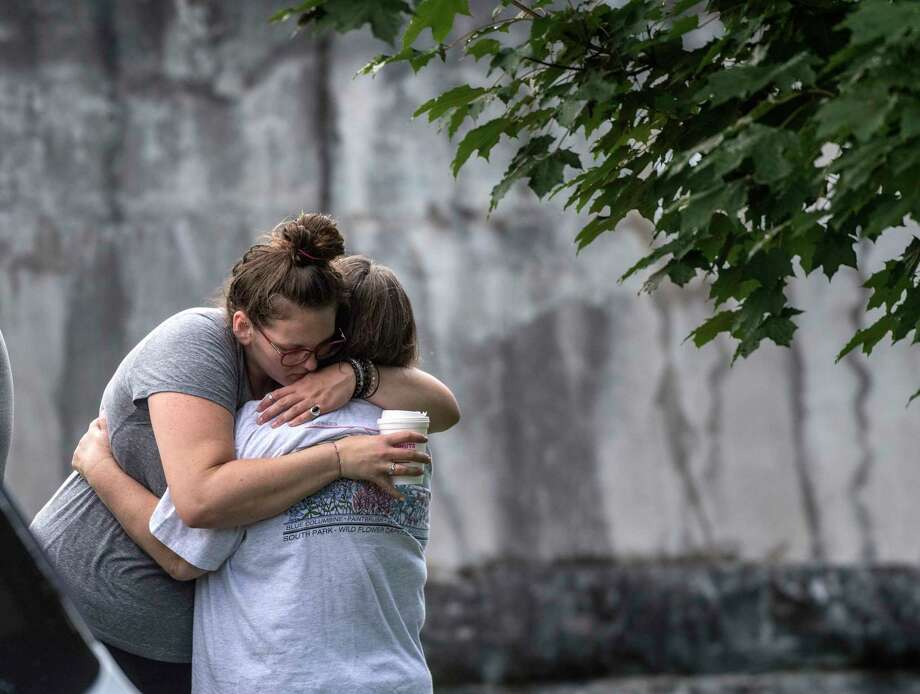 Family members hug near the side of the Mohawk River near Lock 2 as they wait for word of a missing 14 year old male on the Thursday  Aug. 9, 2018 in Waterford, N.Y.(Skip Dickstein Photo: SKIP DICKSTEIN
