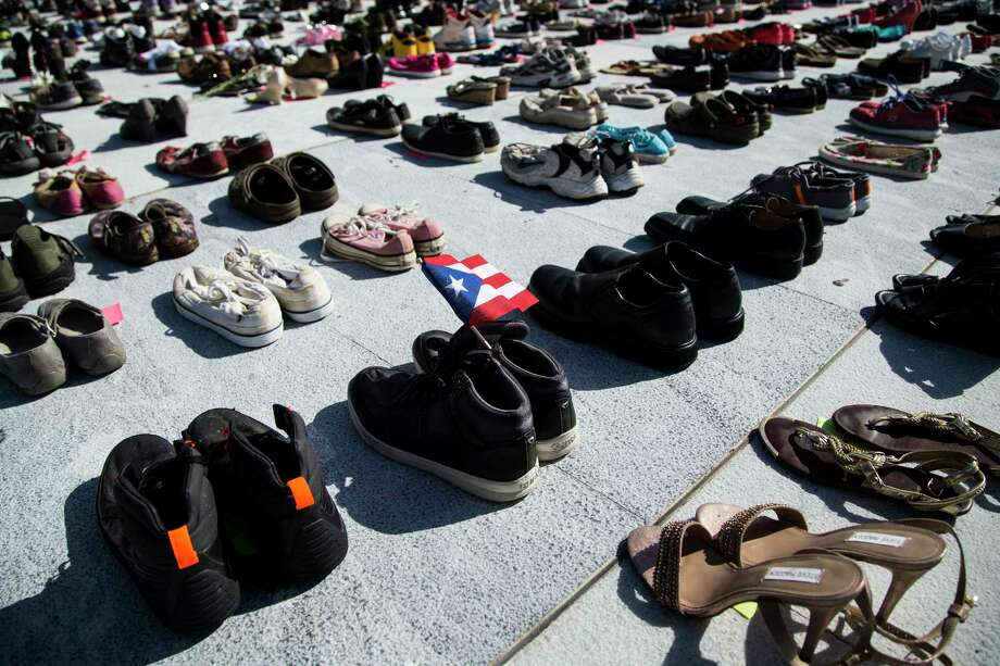 A Puerto Rican flag inside a pair of shoes at a makeshift memorial for the victims of Hurricane Maria, in San Juan, Puerto Rico, June 1, 2018. In a report to Congress requesting recovery funds, the government acknowledged that 1,427 people probably died in Hurricane Maria. The official death toll is 64. (Erika P. Rodriguez/The New York Times) Photo: ERIKA P RODRIGUEZ / NYTNS