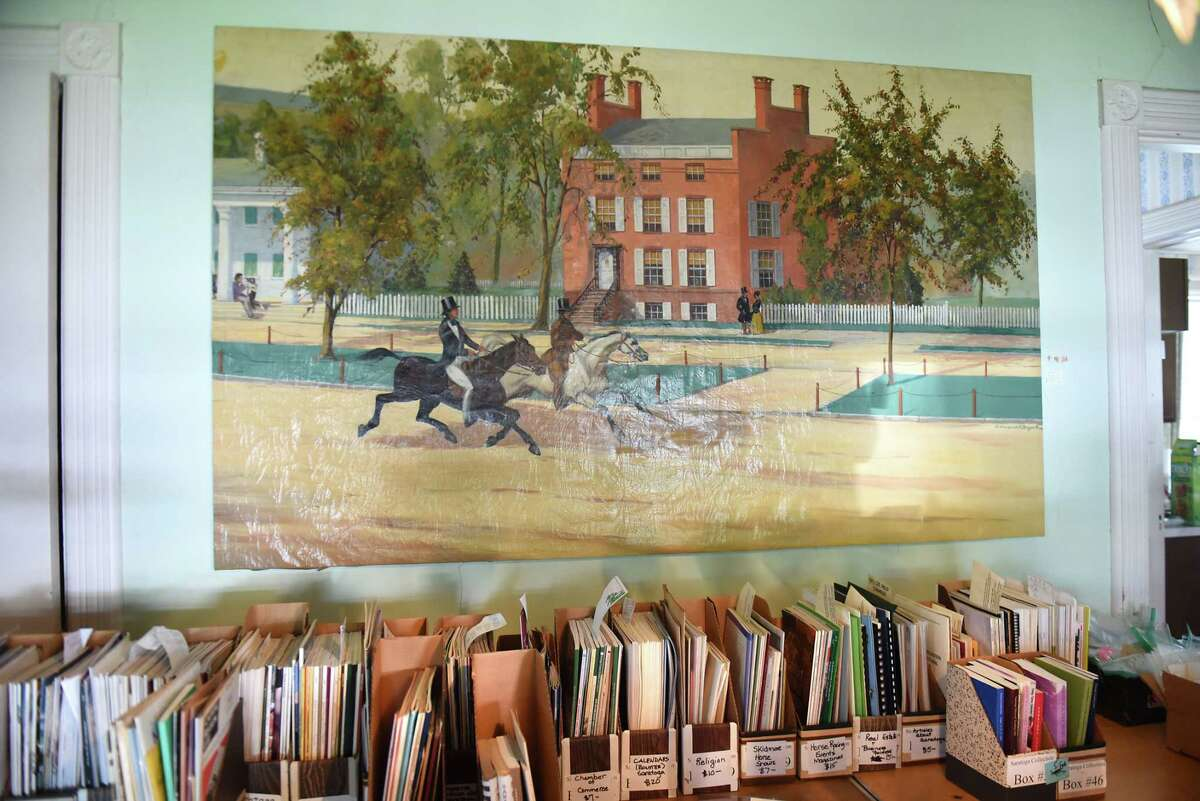 This 1830's painting from the Worden Hotel on Broadway will be for sale at the Saratoga collection of Minnie Clark Bolster estate sale Aug. 9, 2018 in Saratoga Springs, N.Y. The brick building in the painting is where The Wine Bar is now. The sale will take place Friday through Sunday. (Lori Van Buren/Times Union)
