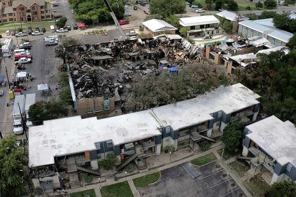 Five people died in a fire July 20 at Iconic Village Apartments in San Marcos. This aerial photo taken July 24 shows the collapsed roof of Building 500 and damage to an adjacent building at Vintage Pads in the foreground.