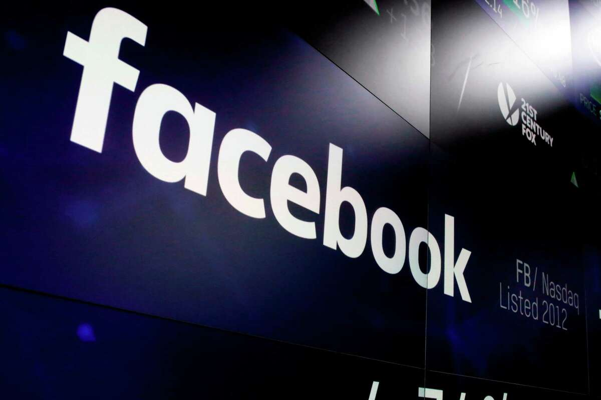 FILE - In this March 29, 2018, file photo, the logo for Facebook appears on screens at the Nasdaq MarketSite in New York's Times Square. Facebook is spending heavily to avoid a repeat of the Russian interference that played out on its service in 2016. Its adversaries are wily, more adept at camouflaging themselves and apparently aren?'t always detectable by Facebook?'s much-vaunted artificial intelligence systems. (AP Photo/Richard Drew, File)