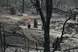 """Loretta Root wipes her eyes while visiting the remains of her home in the Keswick area burned in the Carr Fire, Thursday, Aug. 9, 2018, in Redding, Calif. """"It's hard to see this,"""" Root says of her family home. Several of Root's family members living nearby also lost their homes to the fire. (AP Photo/John Locher)"""