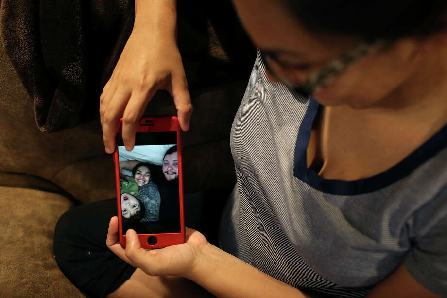 Danielle Kelley shows photos of her with Devin and their son, Michael, 3, at her  Cibolo home on July 10, 2018. (Lisa Krantz | San Antonio Express-News) / San Antonio Express-News