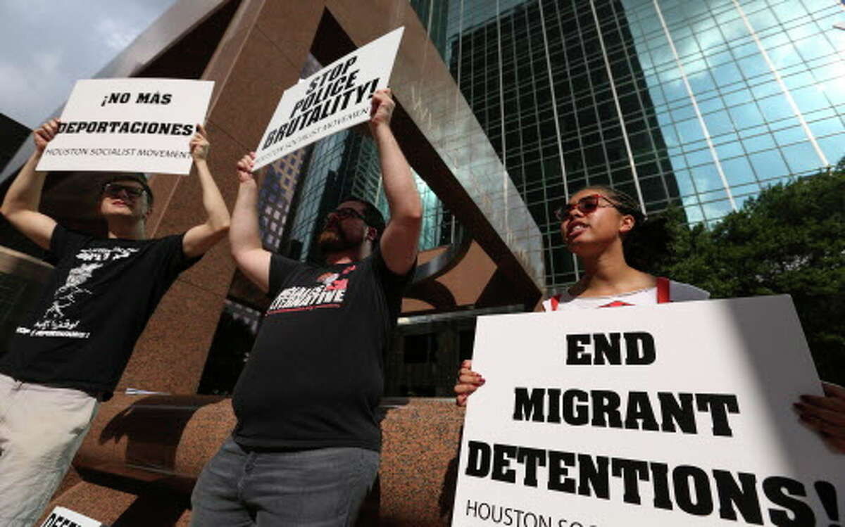 Protesters raise signs and say chants to protest against U.S. Attorney General Jeff Sessions oustide of the United States Attorney's Office for the Southern District of Texas during his brief visits on Friday, Aug. 10, 2018, in Houston.