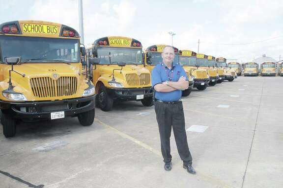 Robert Stock, director of Pasadena ISD's transportation department, stands in front of 32 new seatbelt-equipped buses ready for use when school starts. The district also will open a rebuilt Mae Smyth Elementary School.