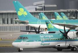 CAPTION CORRECTION, CORRECTS FROM AIG TO IAG IN SECOND SENTENCE - FILE - In this Tuesday, Jan. 27, 2015 file photo, Aer Lingus planes at Dublin airport, Ireland. The Irish government said Tuesday, May 26, 2015 that it intends to sell its 25 percent stake in Aer Lingus to IAG after receiving guarantees that the parent company of British Airways will increase employment and air links with the United States. (AP Photo/Peter Morrison, File)