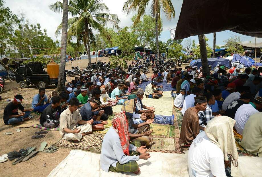 Muslims pray at an earthquake evacuation center in Sambik Bangkol village on Lombok island. A wave of aftershocks since the Aug. 5 quake has fueling a sense that the crisis is far from over. Photo: Sonny Tumbelaka / AFP / Getty Images