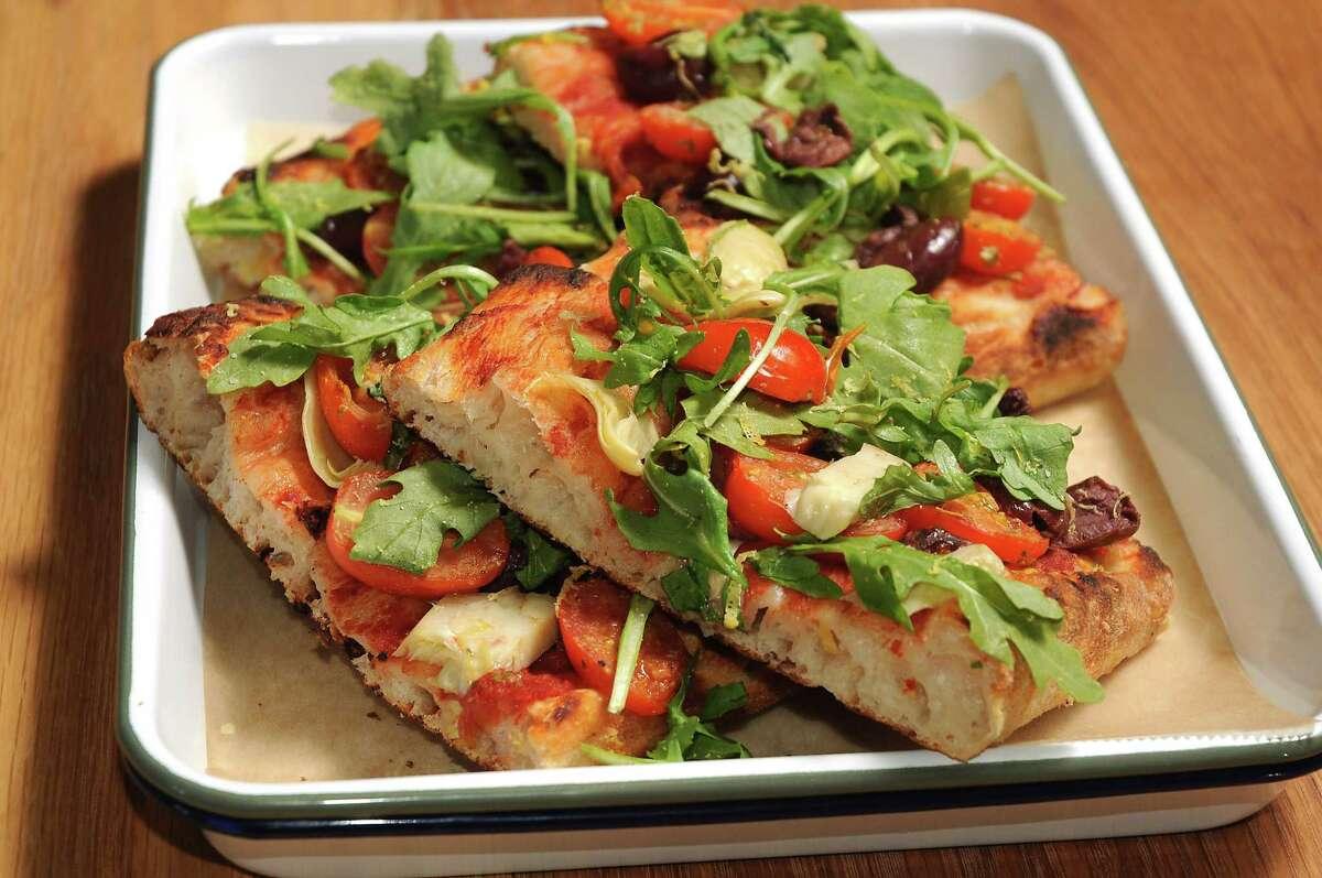 The La Francesca pizza (kalamata olives, goat cheese, sun-dried tomatoes, artichoke hearts and oregano at Pizza Motus, 6119 Edloe, specializing on Roman street pizza or pizza al taglio.