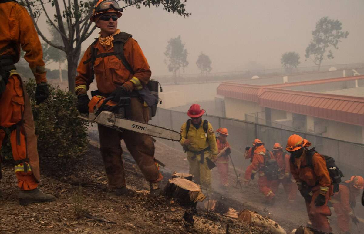 An inmate fire crew clears brush and puts out hotspots to protect an elementary school that almost caught fire at the Holy Fire in Lake Elsinore, California, southeast of Los Angeles, on August 9, 2018. - A man suspected of intentionally starting the Holy Fire on August 6 in the nearby Cleveland National Forest was charged August 9 with multiple felony counts involving arson. (Photo by Robyn Beck / AFP)ROBYN BECK/AFP/Getty Images