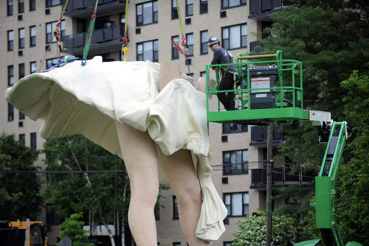 A crew secures the skirt of the 26-foot Marilyn Monroe statue to her legs in Latham Park in downtown Stamford, Conn. on Monday, June 4, 2018. The 30,000 pound statue named