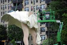 "A crew secures the skirt of the 26-foot Marilyn Monroe statue to her legs in Latham Park in downtown Stamford, Conn. on Monday, June 4, 2018. The 30,000 pound statue named ""Forever Marilyn"" is the largest piece in Stamford Downtown Special Services District's ""Timeless"" series, which also includes 35 life-sized statues by Johnson scattered throughout downtown Stamford."