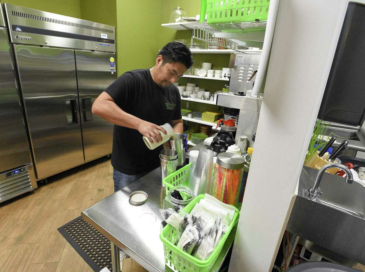 Co-owner Marcial Perez-Saunders makes a smoothie in the new Verde Galerie florist-coffee shop at 79 Atlantic St., in downtown Stamford, Conn., on Aug. 1, 2018.