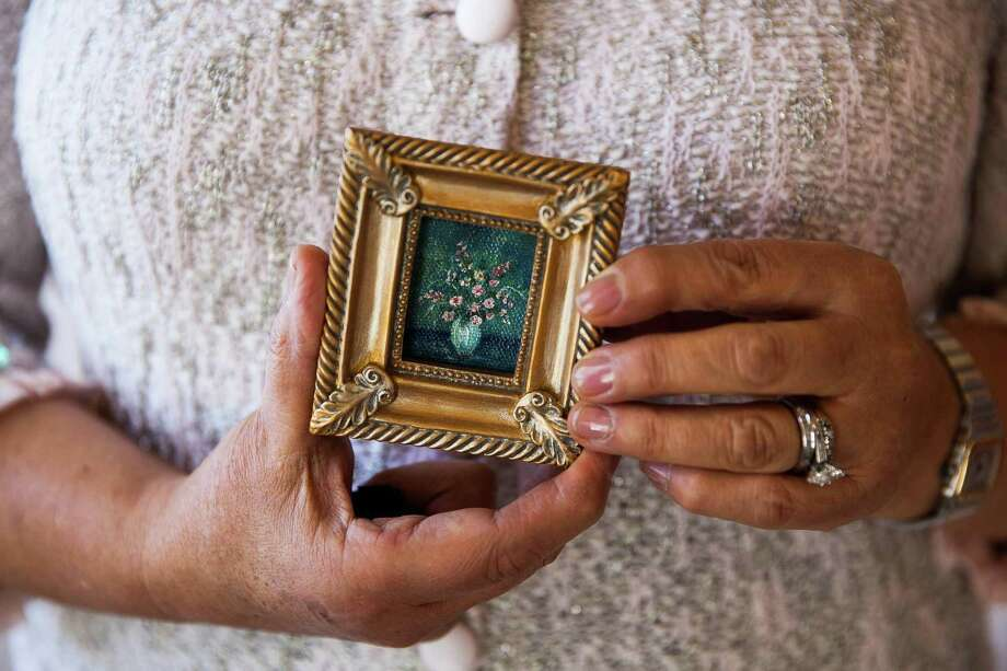 """Artist Martha I. Ochoa holds one of her 5,000 miniature paintings Nov. 22, 2015 at St. Mary's Hall. That was when Ochoa first tried to set a Guinness World Record with her tiny paintings. Guinness World Records later gave her the title of """"largest collection of miniature paintings."""" Photo: Julysa Sosa /Contributor / San Antonio Express-News"""