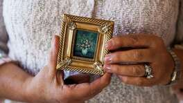 "Artist Martha I. Ochoa holds one of her 5,000 miniature paintings Nov. 22, 2015 at St. Mary's Hall. That was when Ochoa first tried to set a Guinness World Record with her tiny paintings. Guinness World Records later gave her the title of ""largest collection of miniature paintings."""