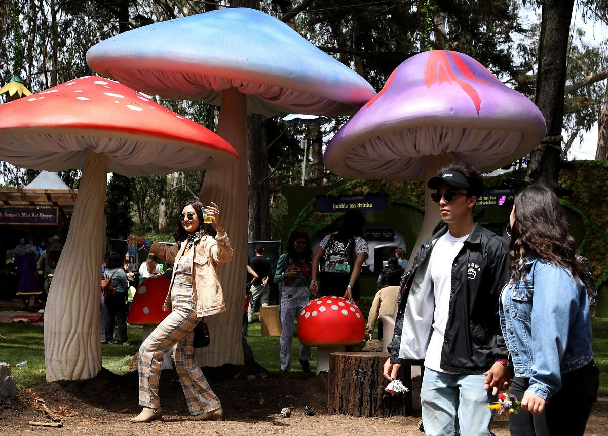 Kiana Pestonjee (name cq'd) poses for a photo in front of gigantic mushrooms in the Grand Artique area at Outside Lands at Golden Gate Park in San Francisco, Calif., on Friday, August 10, 2018.