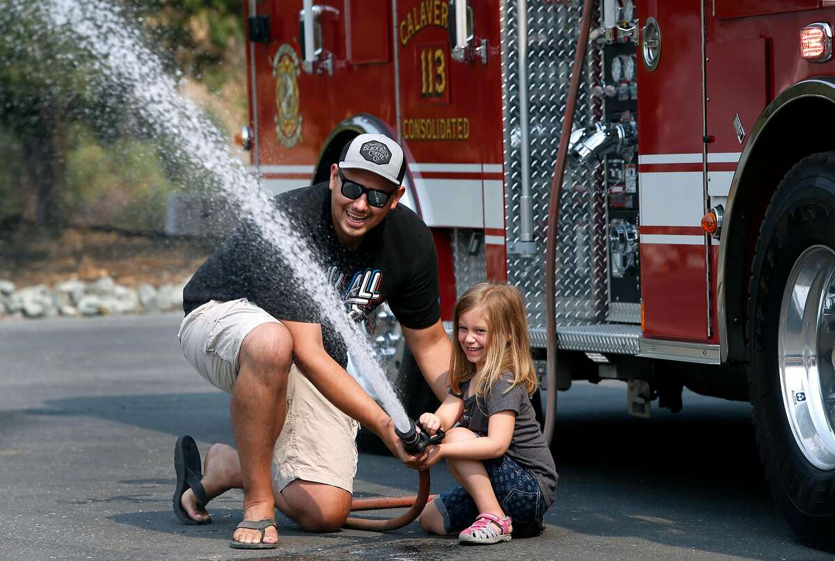 Nicholas Tabakis, a volunteer firefighter for the Calaveras Consolidated Fire Protection District, shows Sienna Archuleta, 5, how to use a fire hose at Station 3 in Valley Springs, Calif. on Tuesday, Aug. 7, 2018. Fire departments throughout California are struggling to recruit volunteer firefighters, which many rural districts rely on.