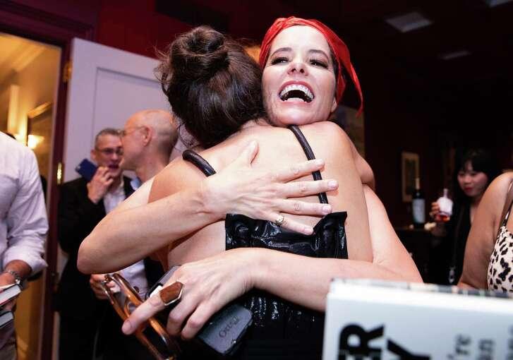 Parker Posey hugs designer Leana Zuniga at her book party.