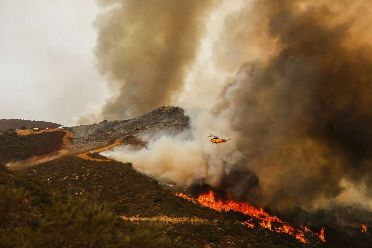 Helicopters drop water on the Holy fire burning through Orange and Riverside counties near Lake Elsinore, Calif., on Friday, Aug. 10, 2018. (Maria Alejandra Cardona/Los Angeles Times/TNS)