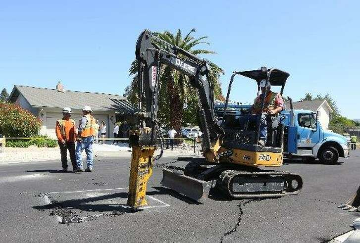 Pg&E crews begin digging up a section of Twin Oaks drive to check for a suspected gas leak that might have occurred after an early morning earthquake Sunday, Aug. 24, 2014, in Napa, Calif.