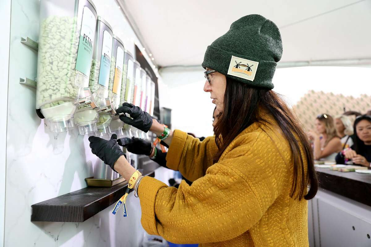 Susan Gentile dispenses mints at the Kiva Confections booth inside the Grass Lands area at Outside Lands at Golden Gate Park in San Francisco, Calif., on Friday, August 10, 2018. Grass Lands is the first marijuana exhibit at a major music festival.