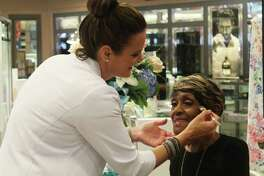 Erin Shipman, Clinique retail business executive, givesDeloice Wilson a surprise makeover at Dillard's in Deerbook Mall on Friday, Aug. 10.
